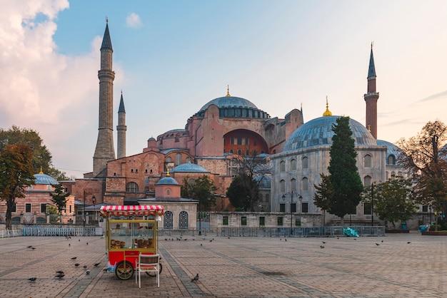 Piękny widok na hagia sophia w stambule w turcji z wózkiem simit na pustym placu o wschodzie słońca. cel podróży