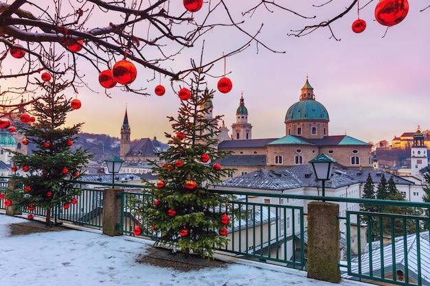 Piękny widok na historyczne miasto salzburg ze słynną katedrą w salzburgu w zimie, austria. choinki z czerwonymi bombkami przeciwko miastu salzburg.