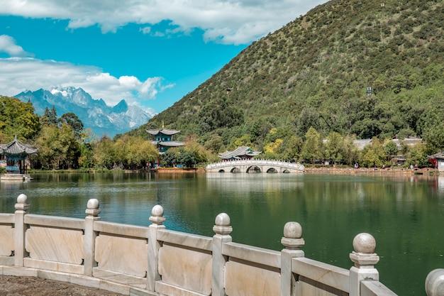 Piękny widok na jade dragon snow mountain i suocui bridge nad black dragon pool w jade spring park, lijiang,