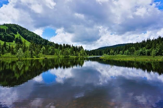Piękny widok na jezioro lispach w alzacji, francja. chmury doskonale odbijają się na czystej, spokojnej wodzie.