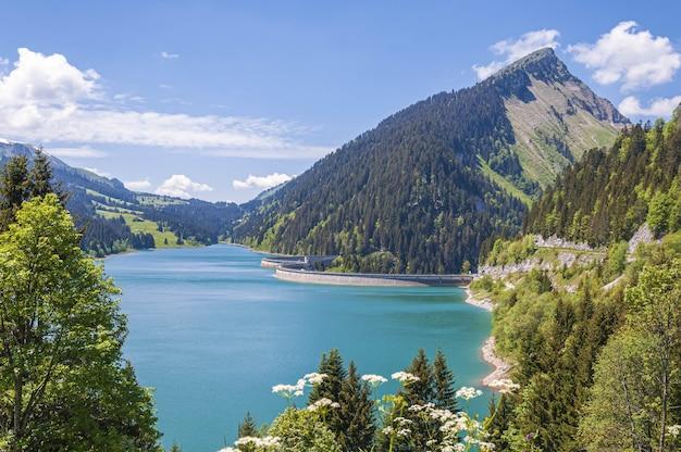Piękny widok na jezioro otoczone górami w jeziorze longrin i tamę w szwajcarii
