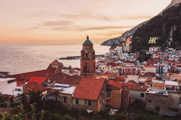 Piękny widok na katedrę i miasto amalfi z kolorowymi domami o zachodzie słońca. wieczorna panorama amalfi z widokiem na zachód słońca i morze. wybrzeże amalfi, włochy
