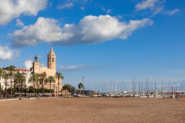 Piękny widok na kościół sant bartomeu i santa tecla w sitges z łodziami na plaży pod pięknym niebem.