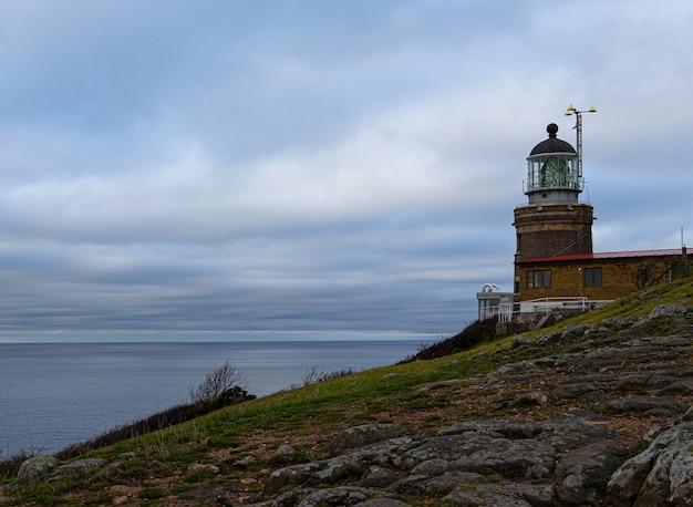 Piękny widok na latarnię morską kullaberg w szwecji z oceanem i pochmurnym niebem