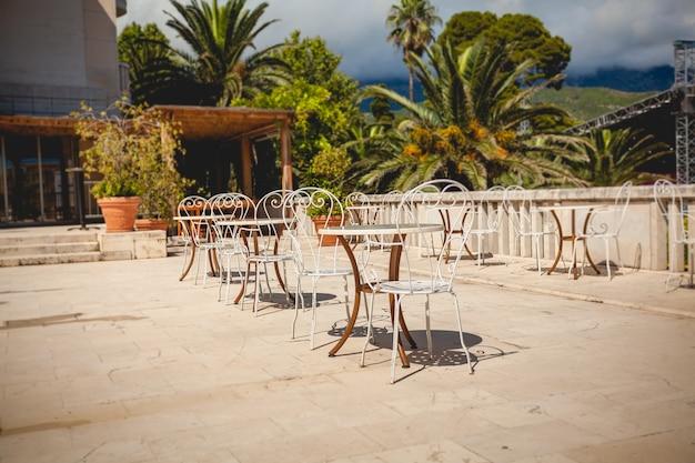Piękny widok na letni taras przy restauracji otoczony zielonymi palmami?