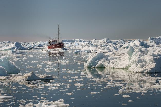 Piękny widok na łódź turystyczną płynącą przez góry lodowe w zatoce disko na grenlandii