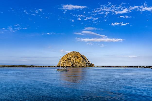 Piękny widok na łódź w pobliżu wyspy na środku oceanu pod błękitnym niebem