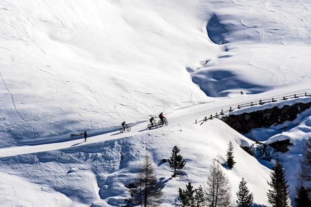 Piękny widok na ludzi jadących na rowerze przez zaśnieżone góry w południowym tyrolu, dolomitach, włoszech