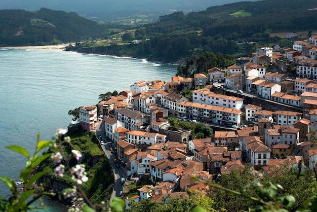 Piękny widok na miasto lastres asturias z kantabryjskim wybrzeżem i górami w tle