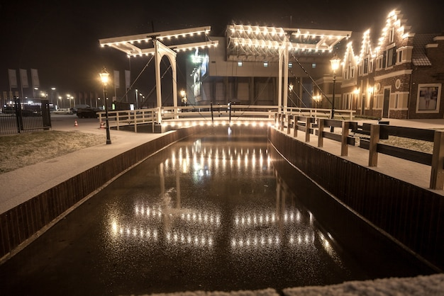 Piękny widok na most zwodzony odbijający się w wodzie w zimową noc