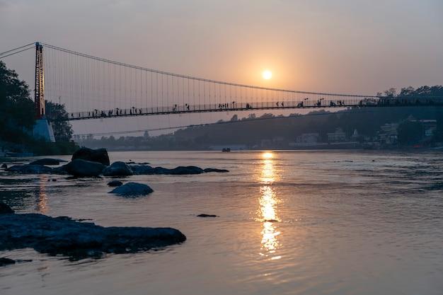 Piękny widok na nabrzeże rzeki ganges i most o zachodzie słońca. rishikesh, indie