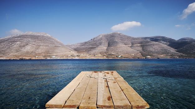 Piękny widok na nikourię z drewnianym pomostem i górami na wyspie amorgos