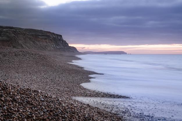 Piękny widok na ocean spotykający się z plażą pokrytą skałami i kamykami o zachodzie słońca w wielkiej brytanii