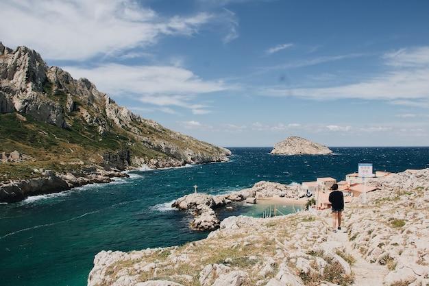 Piękny widok na ogromne skały i całkiem morze z młodą kobietą wędrującą po okolicy, marsylia, francja