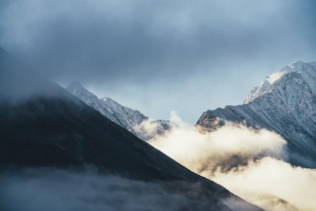 Piękny widok na ośnieżone góry nad gęstymi chmurami w słońcu. malowniczy jasny górski krajobraz z biało-śnieżnym szczytem wśród gęstych niskich chmur na niebieskim niebie. cudowna sceneria ze śnieżnym szczytem.