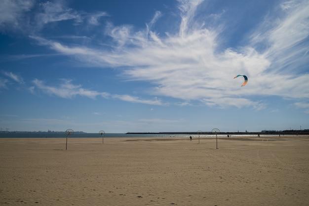 Piękny widok na piaszczystą plażę z zachmurzonym błękitnym niebem