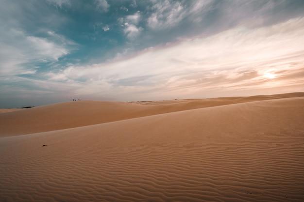 Piękny widok na piaszczyste wzgórza pod zapierającym dech w piersiach pochmurnym niebem