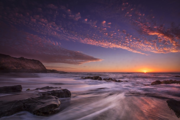 Piękny widok na plażę z czasami podczas zachodu słońca