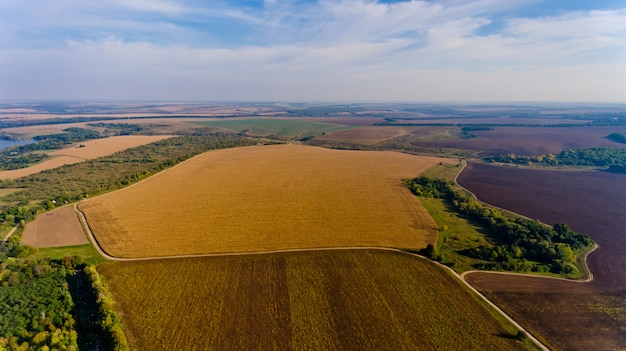 Piękny widok na pola rolnicze i błękitne niebo z białymi chmurami. widok z lotu ptaka.