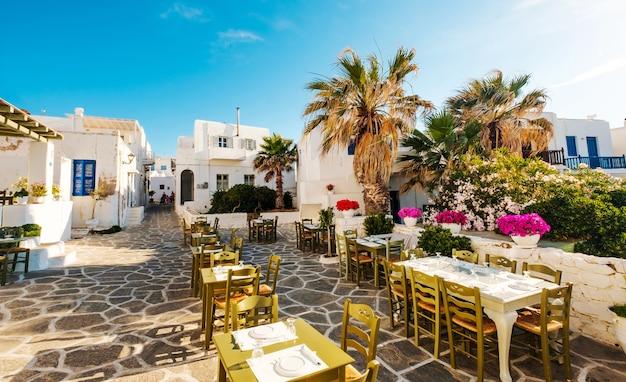 Piękny widok na restaurację i białą architekturę wokół słonecznej greckiej ulicy?