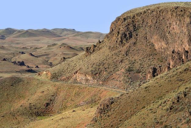 Piękny widok na ścieżkę na zboczu góry ze wzgórzami i błękitnym niebem w tle