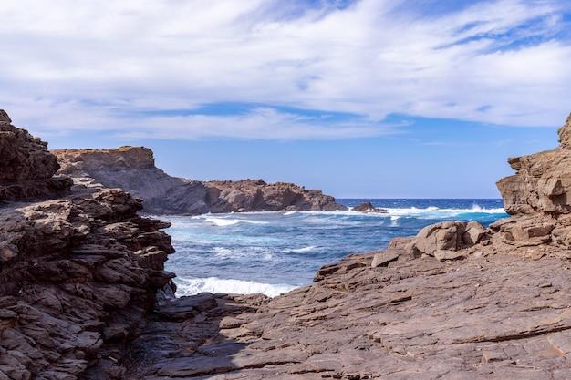 Piękny widok na skalistą zatokę z falami na morzu na wyspie minorka, baleary, hiszpania