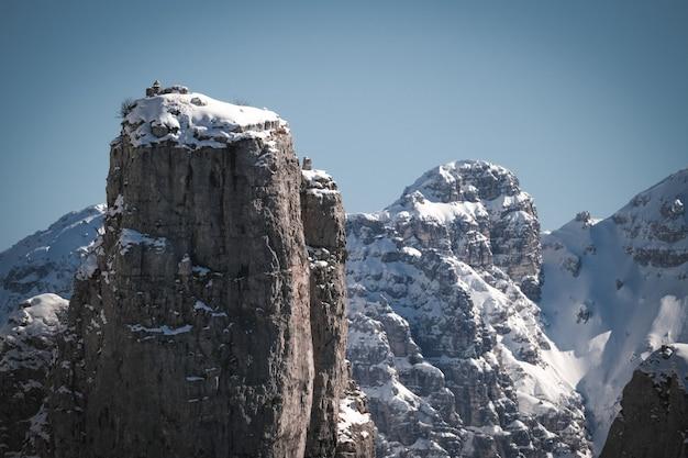 Piękny widok na skaliste klify pokryte śniegiem pod jasnym niebem