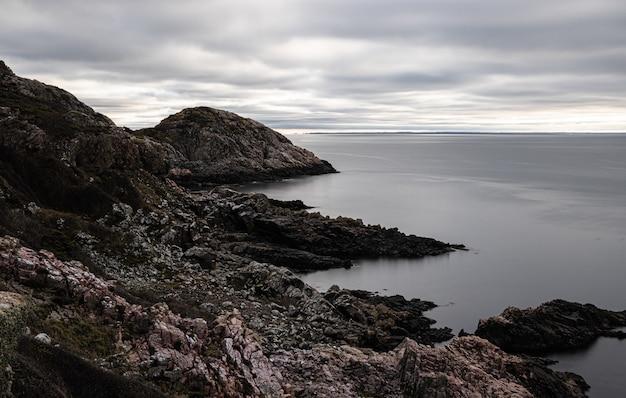 Piękny widok na spokojny ocean i kamienisty brzeg pod zachmurzonym niebem