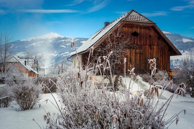 Piękny widok na starą drewnianą stodołę w austriackich alpach pokrytych śniegiem