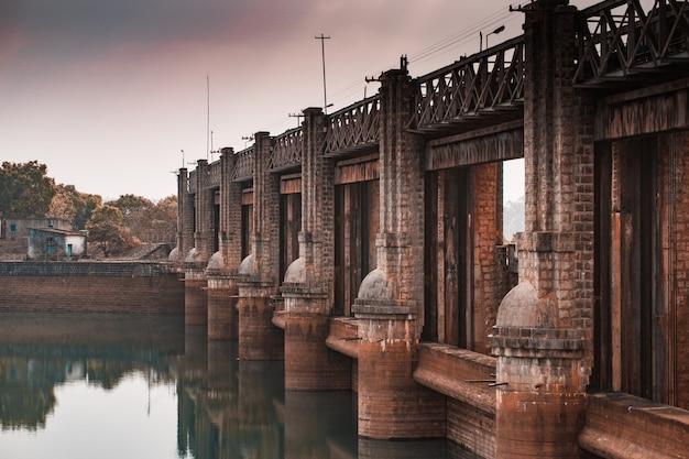 Piękny widok na stary kamienny most odbijający się w czystej wodzie rzeki o świcie
