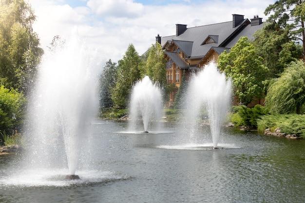 Piękny widok na trzy wysokie fontanny w stawie w luksusowej rezydencji