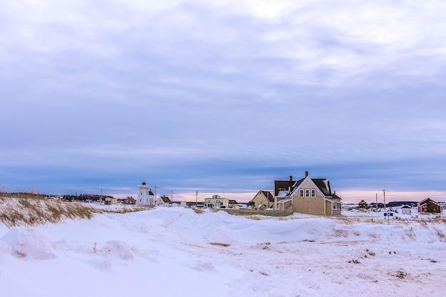 Piękny widok na wiejskie domy pod zachmurzonym niebem w zimie