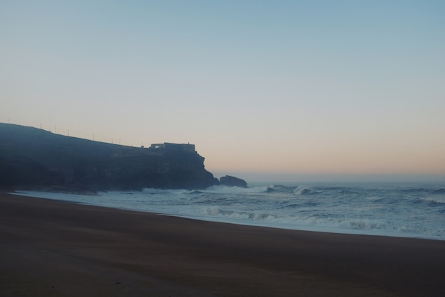 Piękny widok na wielką skałę z zamkiem na szczycie i duże fale ostrzegają o zachodzie słońca
