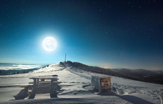 Piękny widok na wielki księżyc i rozgwieżdżone niebo nad zaśnieżonym pagórkowatym terenem leśnym. koncepcja ośrodka narciarskiego w nocy. przestrzeń reklamowa
