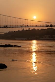 Piękny widok na wodę rzeki ganges i most ram jhula o zachodzie słońca. rishikesh, indie