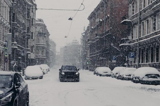 Piękny widok na wspaniałe zaśnieżone miasto z samochodami pokrytymi śniegiem
