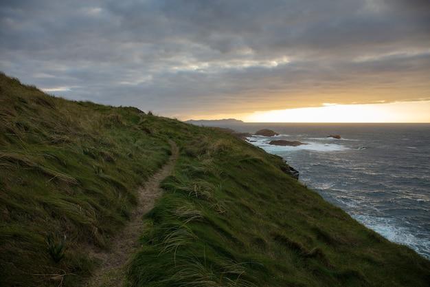 Piękny widok na wybrzeże valdovino pokryte trawą w pochmurny dzień w galicji w hiszpanii