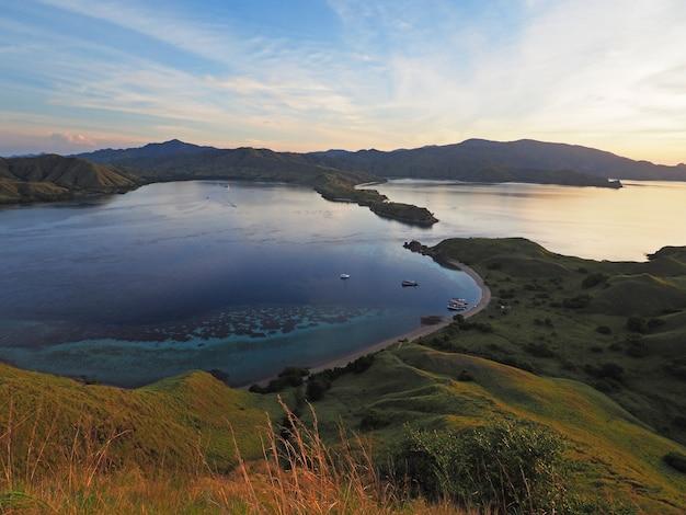 Piękny widok na wyspę z górskim i niebieskim morzem w zachodzie słońca.