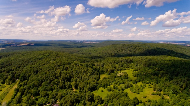 Piękny widok na wzgórze z zielonym lasem i błękitne niebo z białymi chmurami. widok z lotu ptaka.