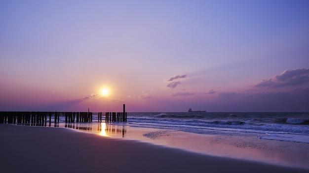 Piękny widok na zachód słońca z fioletowymi chmurami nad plażą