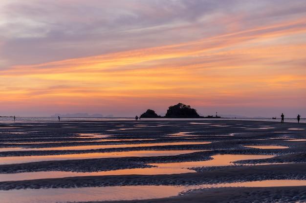 Piękny widok na zachód słońca z wyspy lanta, prowincja krabi, tajlandia południowa, z pięknym półmroku, resztkami wody morskiej na plaży, kilkoma spacerowiczami i małą wyspą