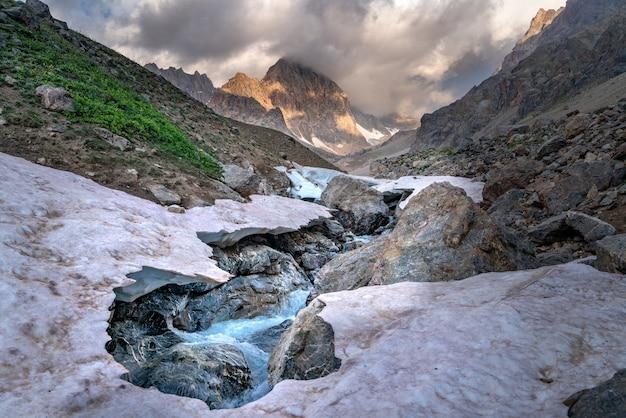 Piękny widok na zamarznięty lodowiec i rzekę kaznok schludną aż po szczyt zmeya w górach fann w tadżykistanie