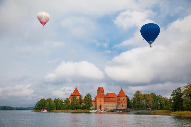 Piękny widok na zamek na wyspie trokai znajdujący się w trokach na litwie, na wyspie na jeziorze galve, a nad nim lecą dwa balony powietrzne