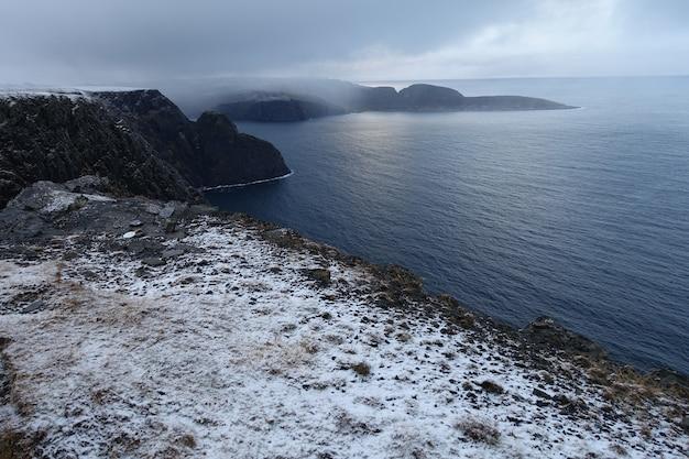Piękny widok na zamglone, pokryte śniegiem klify na wybrzeżu norwegii