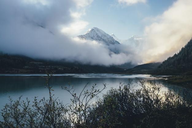 Piękny widok przez sylwetki gałęzi na górskie jezioro i ośnieżone góry nad gęstymi chmurami w słońcu. malowniczy alpejski krajobraz ze szczytem białego śniegu wśród gęstych niskich chmur w rozmyciu.