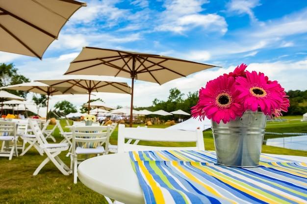 Piękny widok różowych kwiatów w koszu na stole z parasolami w ścianie