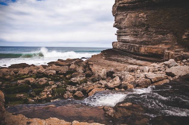 Piękny widok spienioną falą na wybrzeżu w pobliżu klifu