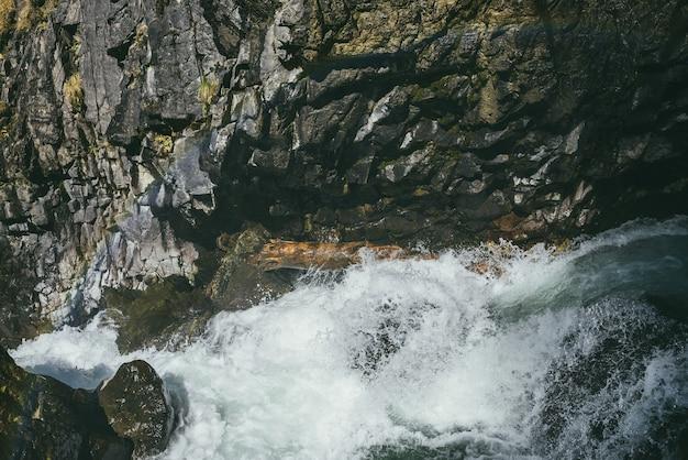 Piękny widok z góry na turkusową, burzliwą górską rzekę wśród skał w wąskim wąwozie w słońcu. atmosferyczny krajobraz górski z mokrymi omszałymi kamieniami w potężnej górskiej rzece w słońcu.