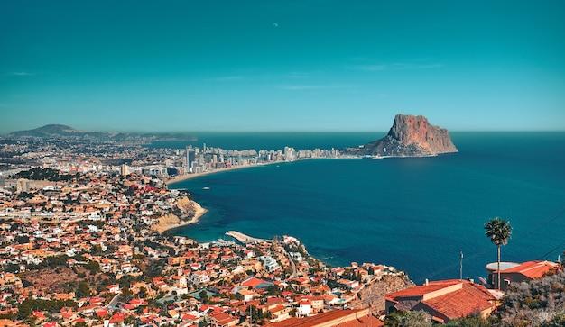 Piękny widok z klifu na nadmorskie miasteczko nad morzem z wieloma małymi budynkami przy słonecznej pogodzie.