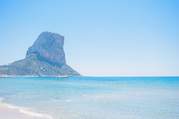 Piękny widok z plaży na słynnej skale penon de ifach na costa blanca, miasto calpe, hiszpania.